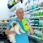 Positive man with dog looking new bowl in pet store, woman on background